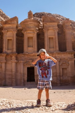 Young boy smiles in front of the Monastery in Petra