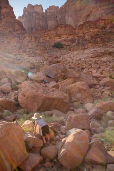 Young boy wearing a hat climbs over the red rocks of the Wadi Rum desert