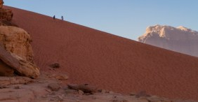 A couple climbs near the top of a tall red sand dune