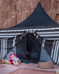 Father and son snuggle in front of a tent in Wadi Rum