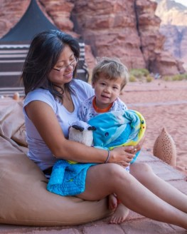 Woman and toddler snuggle in front of a desert camp
