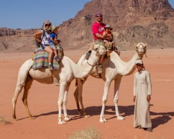 Family rides camels through Wadi Rum