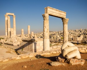 The Hand of Hercules, a giant sculpture sits in front of Roman ruins - Traveling Jordan with Kids