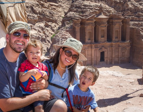 Family smiles in front of the Monastery in Petra