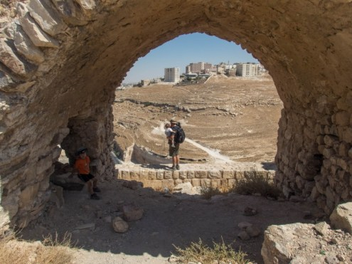Young boy sits in a tunnel while his Dad takes in the view from the other side