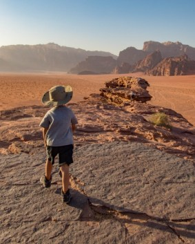 Young boy wearing a hat looks out over an epic landscape of the Wadi Rum desert