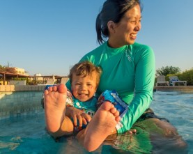 Mother and son splashing in a pool at the Radisson Blu Resort near the Red Sea, Jordan.