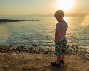 Young boy watches the sunset over the Dead Sea at the Kempisnki Hotel