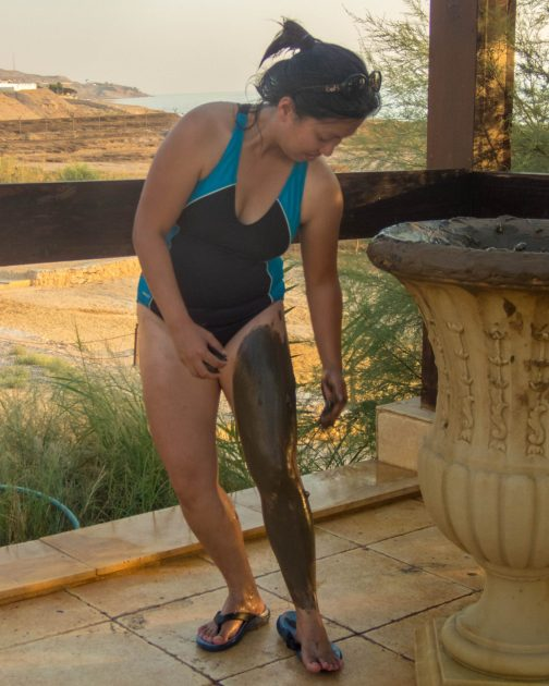 Woman putting on mud from the dead sea