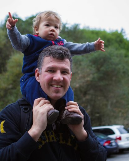 Father with son on his shoulder at parking lot of Muir Woods National Monument