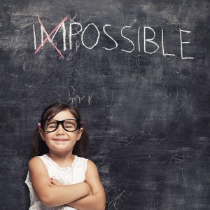 Confident young girl in front of chalk board with IM scratched out of Impossible. Travel with kids promotes self confidence in children, as well as teaching parents to trust their little ones.