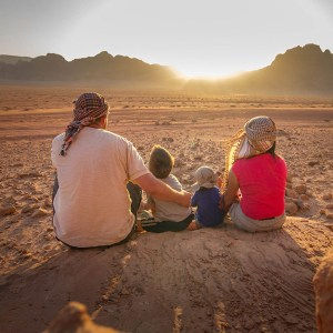 Father, Mother and two young boys watch a sunset in the desert showing the benefits of travel with kids