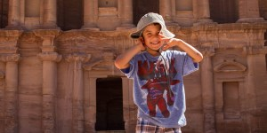 Young boy smiling and holding his hat in front of Petra's Monastery