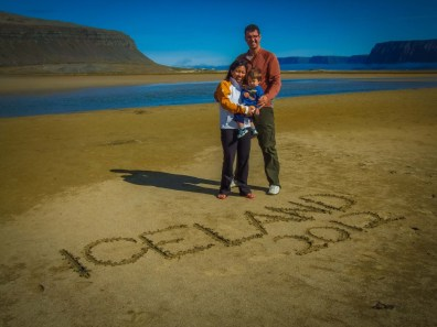 a family of three stands on a beach in front of Iceland 2012 written in the sand
