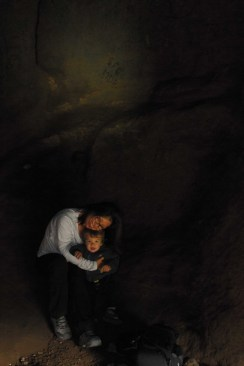 Mother and son inside cave with writing on wall