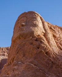 The face of an indigenous person is carved into the cliffs near San Pedro de Atacama