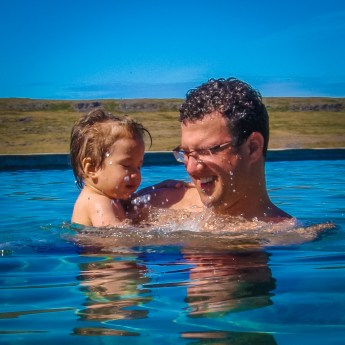 Father and young boy splash in an outdoor pool