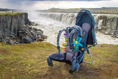 Kid carrier Deuter Kid Comfort III on grass at the top of of a cliff in front of waterfalls