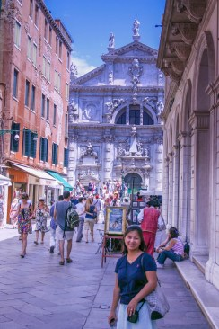 Smiling tourist woman stands in the crowd in Venice - lost in Venice