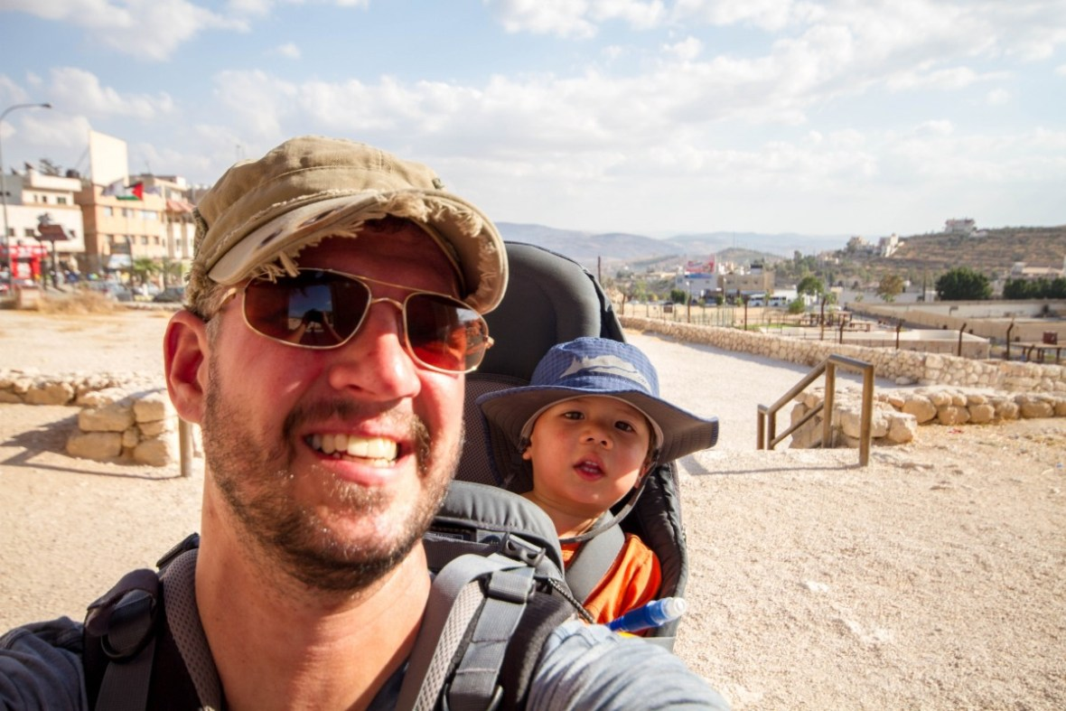 Man smiles for the camera with a child in a kid carrier - Deuter Kid Comfort III