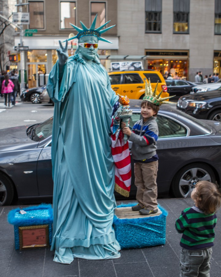 Young boy smiles while holding a torch with a street performer in a statue of liberty costume
