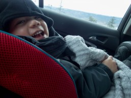 Young boy in car seat smiling - Learning to Ski at Kelowna's Big White