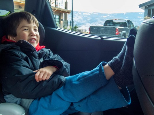 Young boy relaxes while driving up a mountain - Learning to Ski at Kelowna's Big White