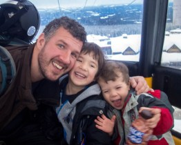 Dad and two young sons riding in a gondola smile and laugh - Learning to ski at Kelowna's Big White