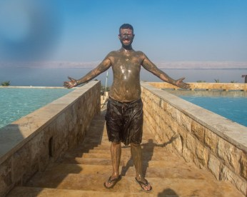 Smiling man covered in mud holds his arms out in front of the Dead Sea at the Kempisnki Hotel