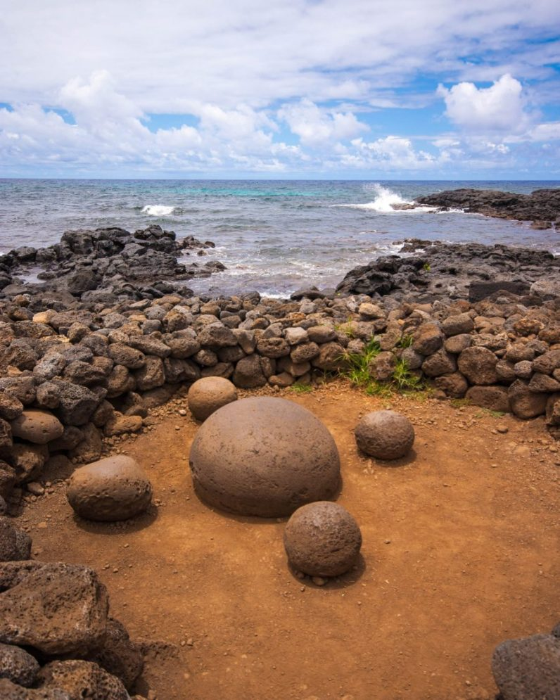 A large round rock is circled by four smaller round rocks sitting on red ground within a stone foundation. Blue skies and a wavy ocean are in the background