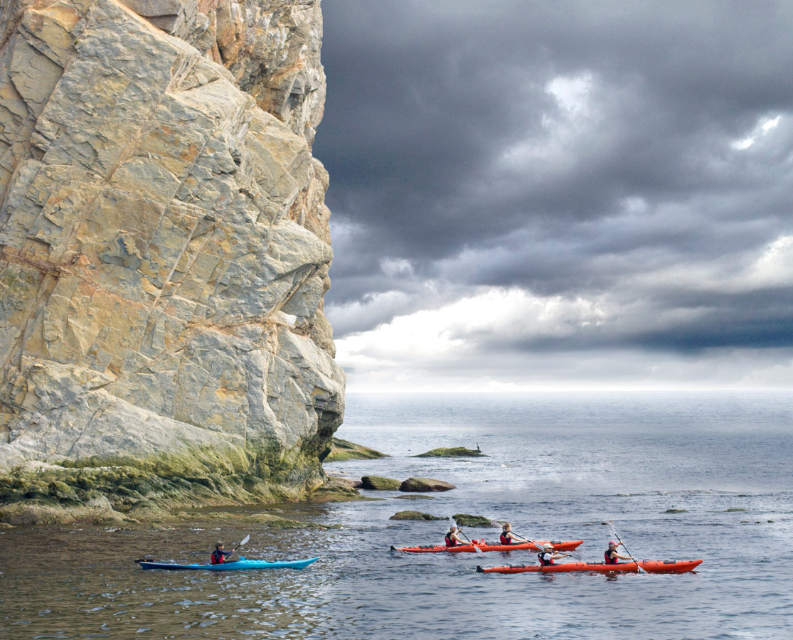 Kayakers explore the area around Perce Rock near Bonaventure Island on the Gaspe Peninsula of Quebec