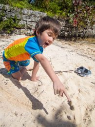A young boy makes a sand dinosaur on a break while boating in Bermuda.