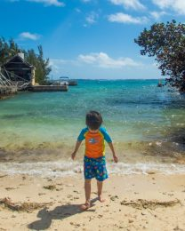 A young boy in swim gear walks out of the waves of a small cove in Bermuda - Boating in Bermuda