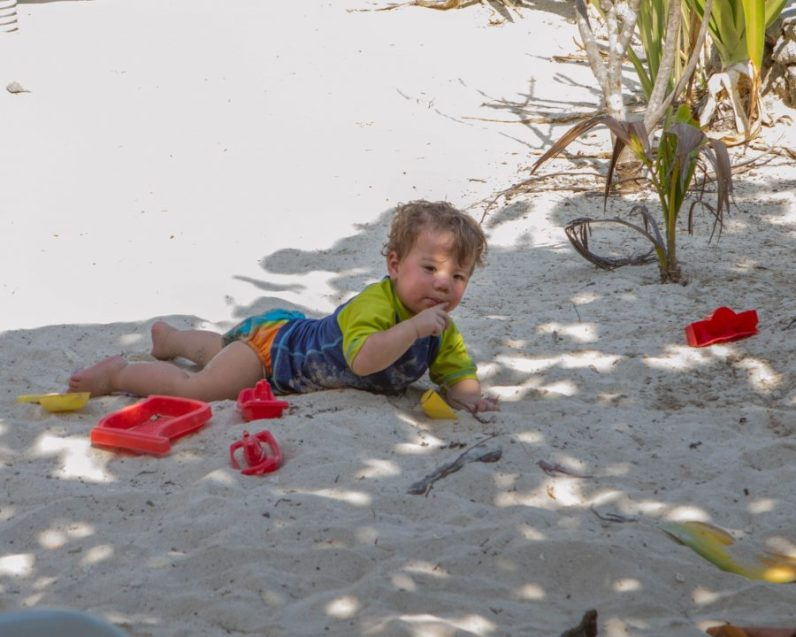 Boy laying on the sand with sand toys around him in Pirate Island.