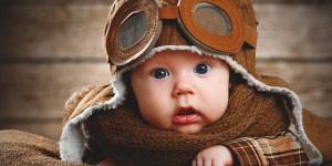 Baby in a vintage pilots outfit looking at the camera - Flying with a baby
