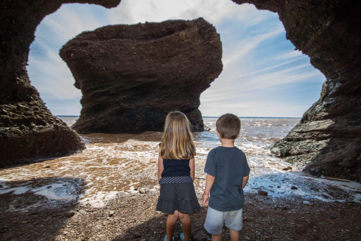 Children on the ocean floor looking at Hopewell Rocks one of our bucket list destinations in Canada.