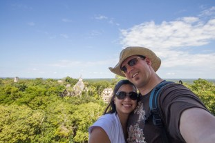 A woman and a man take a selfie on a pyramid overlooking Mayan ruins within the Guatemalan jungle