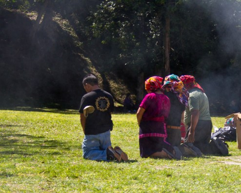 local Mayans prayer while surrounded in smoke near a Mayan ruin