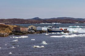 Fishing huts and boats by the dock with ice floes in the ocean.
