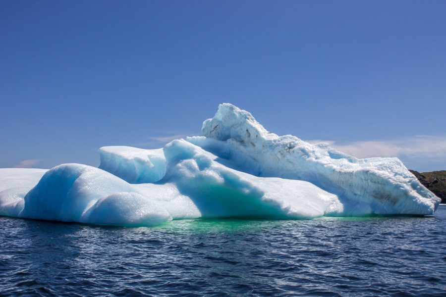 A deeply layered iceberg in the Newfoundland Iceberg Alley with the deep water showing the depth that the iceberg sinks to - Icebergs in Twillingate
