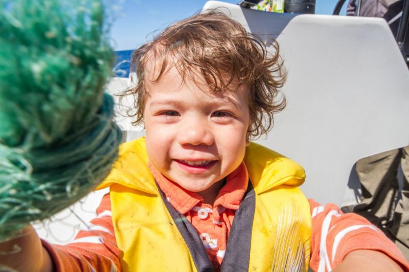 Smiling boy wearing an orange shirt and life jacket rides in a boat - Icebergs in Twillingate