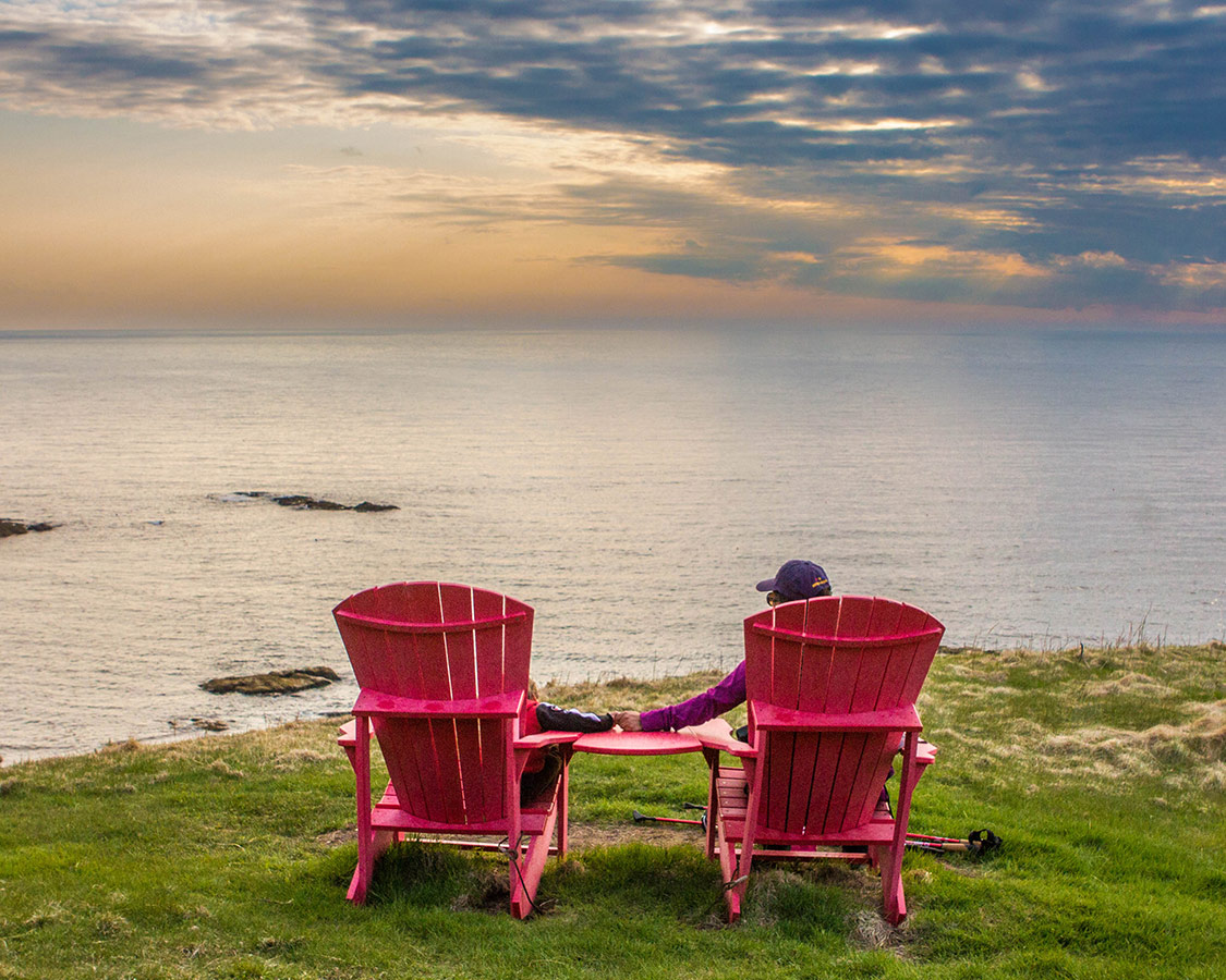 A woman and a toddler hold hands in large red muskoka chairs while watching the sunset at the top of a cliff overlooking the ocean - Hiking Green Gardens in Gros Morne National Park