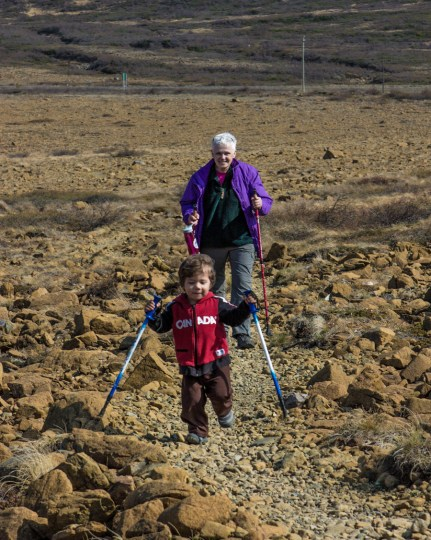 An older woman and a smiling toddler hike along a rocky trail in Gros Morne National Park - Hiking Green Gardens in Gros Morne National Park
