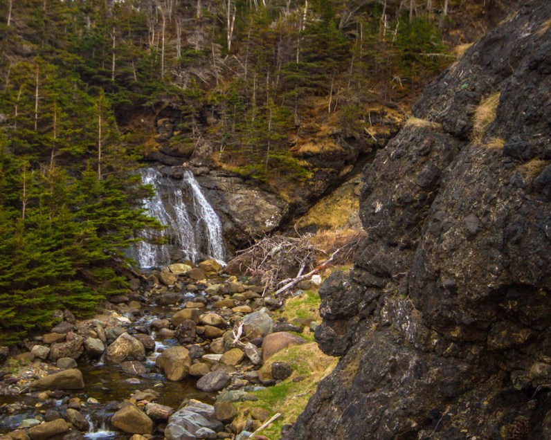 A waterfall pours from the forest and into a rocky stream in Gros Morne National Park - Hiking Green Gardens in Gros Morne National Park