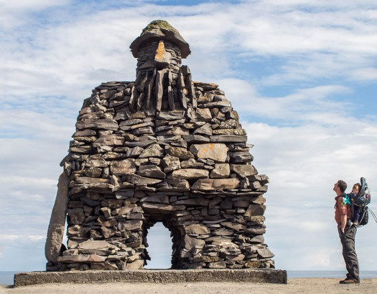 A father and son stare up at an Icelandic sculpture on the coast