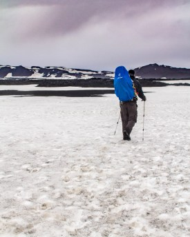 A man carrying a kid-carrier hikes along a snowy mountaintop - An Epic 14 Day Iceland Itinerary