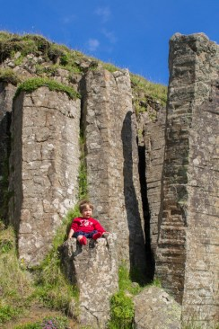 A young boy sits on a basalt column - An Epic 14 Day Iceland Itinerary