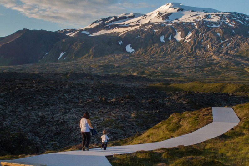 A woman and a young boy walk down a white path with snow capped mountains in the background - An Epic 14 Day Iceland Itinerary