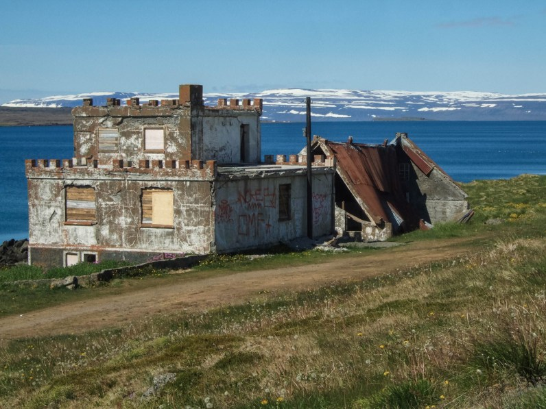 A castle style house lies in ruins near a lake in Iceland - An Epic 14 Day Iceland Itinerary