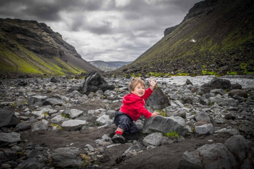 A young boy plays on rocks in an Icelandic river - An Epic 14 Day Iceland Itinerary